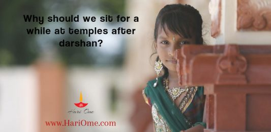 Why should we sit for a while at temples after darshan?